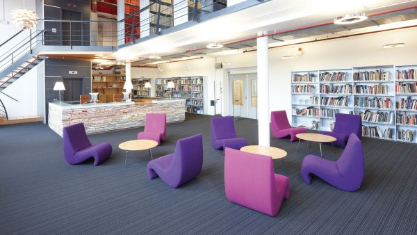 Amoebe Lounge Chair in violet and purple in a library setting with other furniture