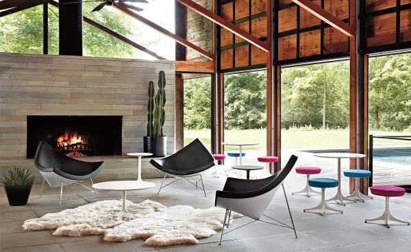 Black Nelson Coconut Chair with white frame and metal support and legs featured in a living room setting with other furniture