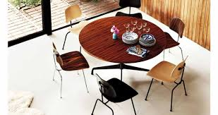Eames plywood wood pattern table featured in dining setting with other furniture