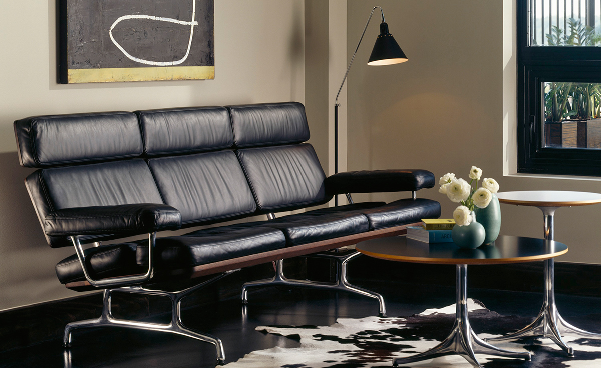 Eames Sofa with high back and artmrest with metal legs featured in an office setting with other furniture