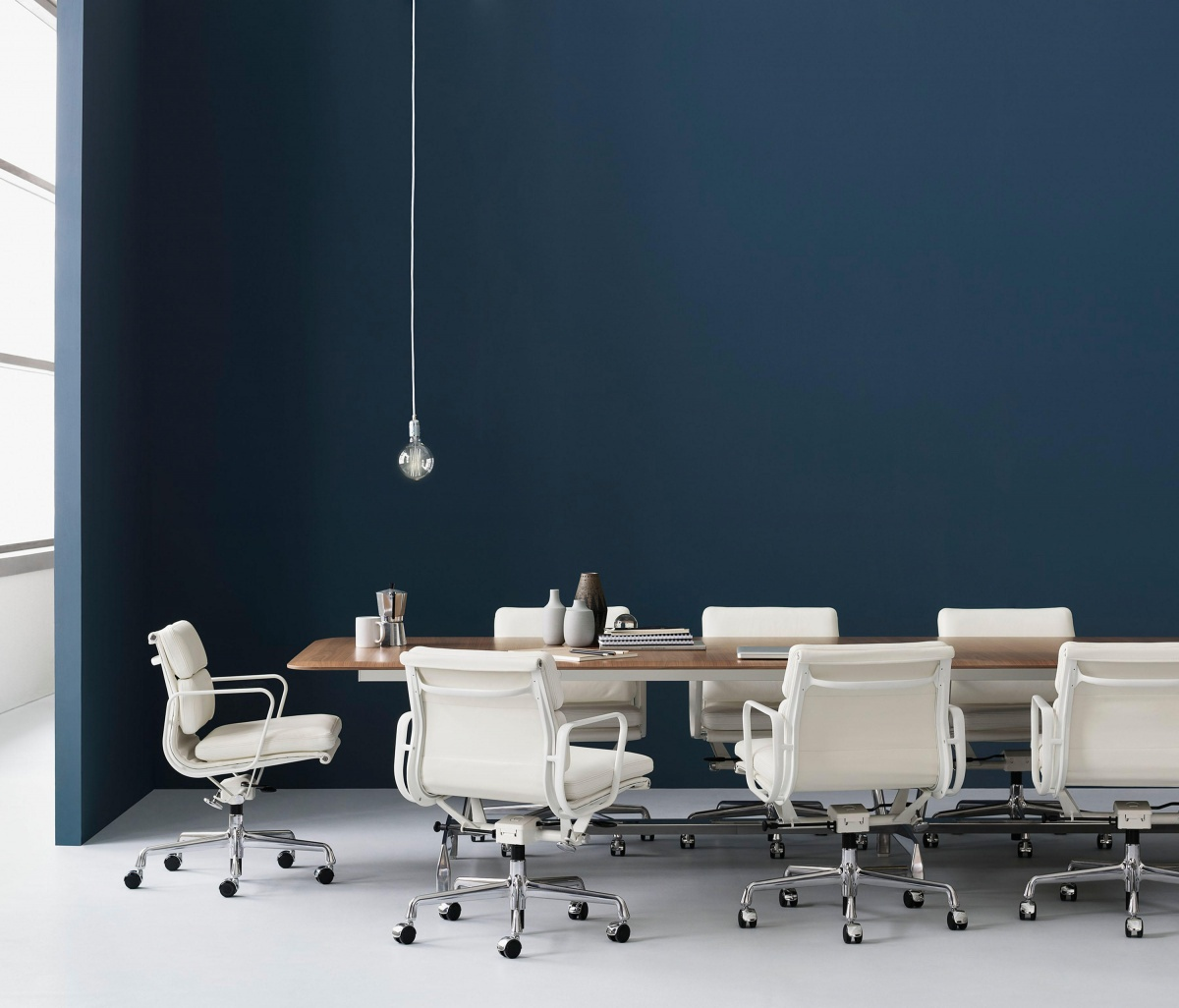 White Eames Aluminum Office Chair featured in office setting with other furniture