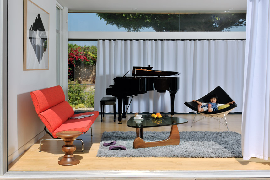 Red Eames Compact Sofa featured in a living room setting with other furniture