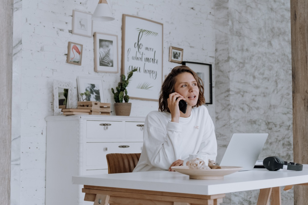 woman on the phone at her home office desk