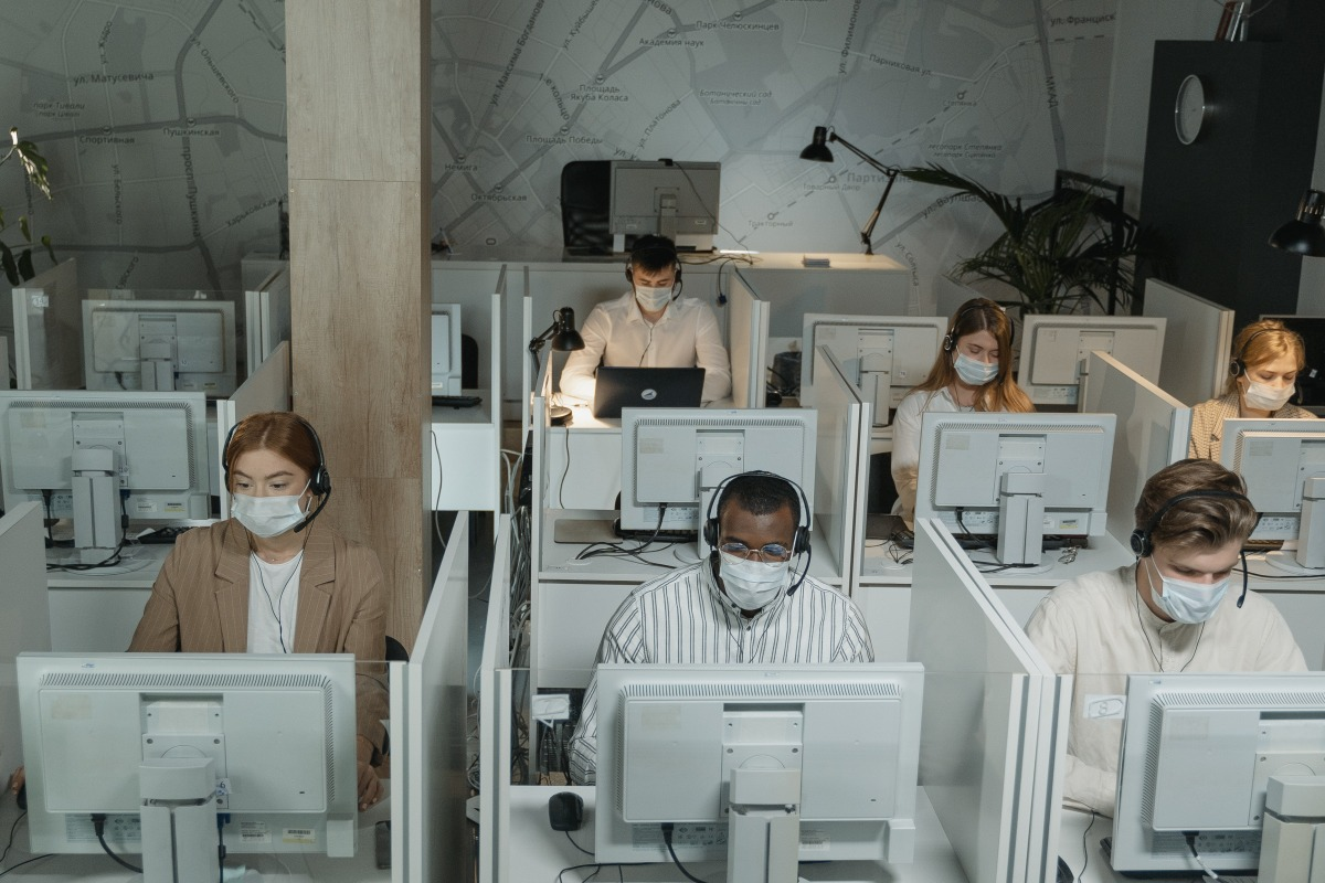 workers on their desks and masks on