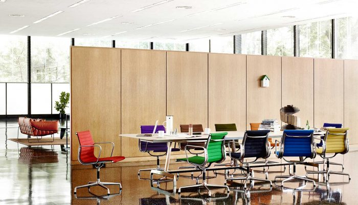 Eames Aluminum Multi-Coloured Chairs featured in an office setting with other furniture